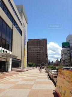 街の通りに看板が立つ大きなレンガ造りの建物の写真・画像素材[2714150]