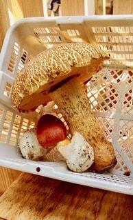 木製のテーブルの上に座っている食べ物でいっぱいのバスケットの写真・画像素材[2720676]
