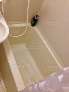 シャワーの隣に座っている白い浴槽の写真・画像素材[2761147]