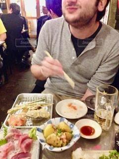 食べ物の皿を持ってテーブルに座っている男の写真・画像素材[2761151]