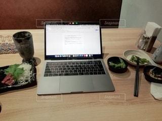 木製のテーブルの上に座っているラップトップコンピュータの写真・画像素材[3430430]