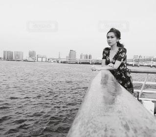 水の体の横に立っている人の写真・画像素材[913328]