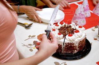 皿の上でケーキを切る女性の写真・画像素材[2298388]