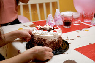 バースデーケーキを持ってテーブルに座っている女性の写真・画像素材[2298390]