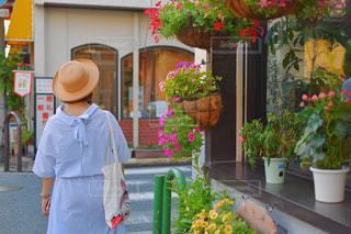 花の前に立っている人の写真・画像素材[1565673]