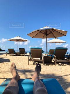 ビーチの上に座っている青い傘の写真・画像素材[2094551]