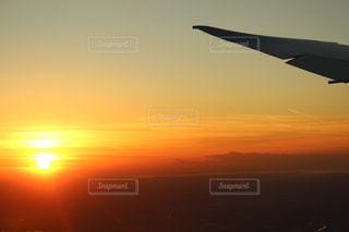 夕日で空を飛んでいる飛行機の写真・画像素材[939252]