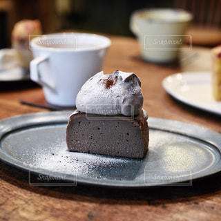 コーヒー カップの横にある皿の上のケーキの一部の写真・画像素材[1089358]