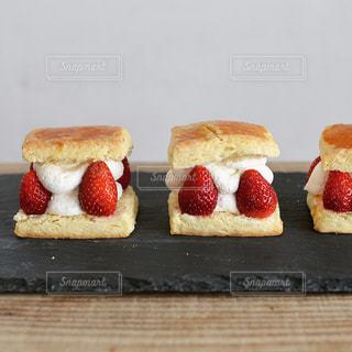 木製テーブルの上にフルーツとケーキの写真・画像素材[1875215]