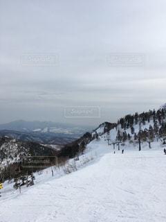 雪に覆われた斜面をスキーに乗っている人のグループの写真・画像素材[1039625]