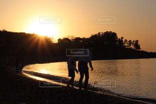 夕日の前を歩いている男の写真・画像素材[2136988]