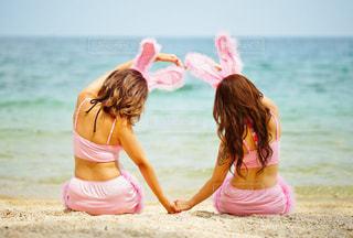 砂浜に座っている女の子の写真・画像素材[708910]