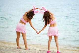 ビーチの砂の上に立っている少女の写真・画像素材[708911]