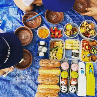 食物と一緒にテーブルに座っている人々 のグループの写真・画像素材[1155647]