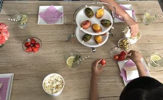 食物と一緒にテーブルに座って人の写真・画像素材[1167844]