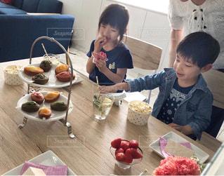 食物と一緒にテーブルに座っている人々 のグループの写真・画像素材[1169728]