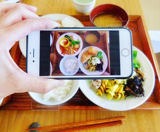 テーブルに食べ物のプレートを持っている人の写真・画像素材[1192242]