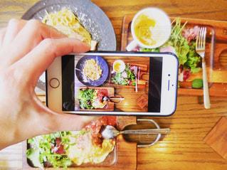 テーブルに食べ物のプレートを持っている人の写真・画像素材[1194007]
