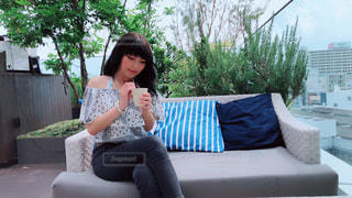 ソファの上に座っている女性の写真・画像素材[1223036]