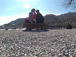 岩の多いビーチに座っている男の写真・画像素材[1842388]