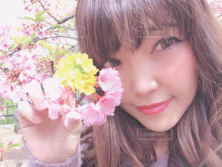 近くにピンクの花の女の子のアップの写真・画像素材[1866583]