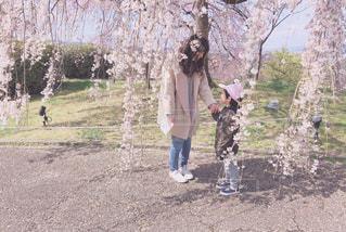 木の隣に立っている女の子の写真・画像素材[1878417]