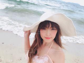 水域の近くの浜辺に立っている人の写真・画像素材[2138415]