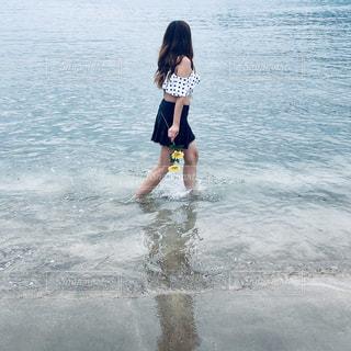 水の体の隣に立っている若い女の子の写真・画像素材[2297198]