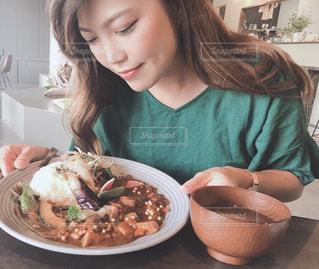 食べ物の皿を持ってテーブルに座っている女性の写真・画像素材[2409000]