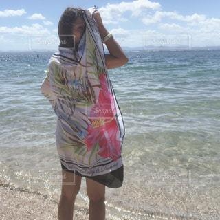 水域の近くの浜辺に立っている人の写真・画像素材[2425580]