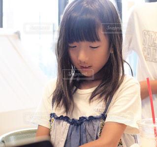 テーブルの上に座っている若い女の子の写真・画像素材[2445081]