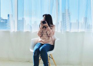 椅子に座って携帯電話で話している女性の写真・画像素材[2725067]