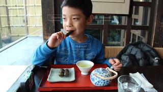食べ物を食べているテーブルに座っている少年の写真・画像素材[3064179]