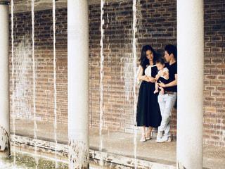 レンガ造りの建物の前に立っている人々のグループの写真・画像素材[3296672]