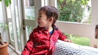 窓の前に座っている小さな女の子の写真・画像素材[3664820]