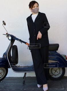 バイクの前に立っているスーツを着た男の写真・画像素材[4379688]