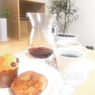 食品やコーヒー テーブルの上のカップのプレートの写真・画像素材[1594726]