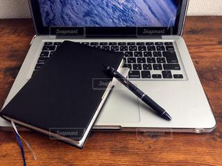 机の上のノートパソコンとビジネス手帳の写真・画像素材[1039840]