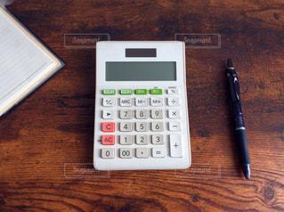 木製デスクの上にある電卓の写真・画像素材[1039841]
