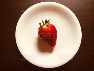 皿の上にあるひとつの苺の写真・画像素材[1057091]
