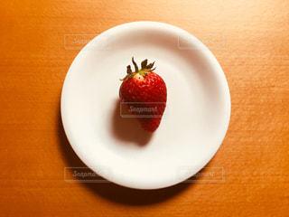 お皿の上にある1つの苺の写真・画像素材[1057095]