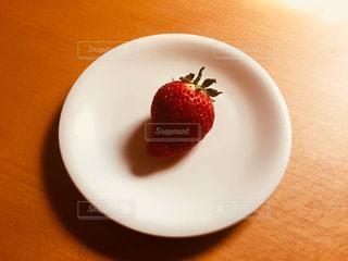 お皿の上にあるひとつのいちごの写真・画像素材[1057096]