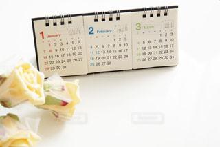 小さい卓上カレンダーと白い薔薇の花の写真・画像素材[1482506]