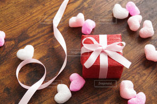 木製テーブルの上のプレゼントとハートの写真・画像素材[1764553]