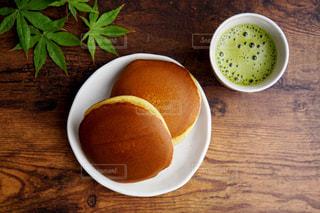 一杯の抹茶の隣にある皿の上のどらやきの写真・画像素材[2168437]
