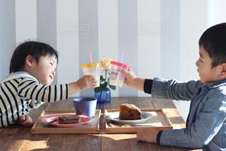 テーブルに座って乾杯する男の子の写真・画像素材[1776807]