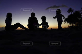 夕焼けのビーチ沿いにいる家族の写真・画像素材[1782682]