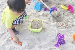 浜辺に座っている小さな男の子の写真・画像素材[2093602]