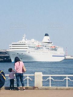 水の大きな船の前に立っている人々 のグループの写真・画像素材[1098856]
