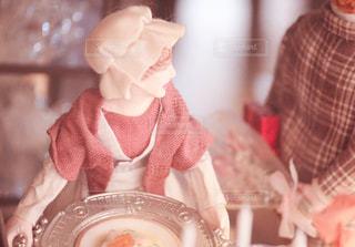 皿の上のケーキをテーブルに着席した人 - No.1108034